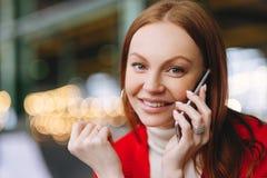 O tiro ascendente próximo de negociações despreocupadas atrativas de estudante fêmea no telefone celular, aprecia a conversação c imagens de stock