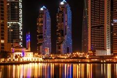 O tiro bonito do porto de Dubai eleva-se e mesquita na noite imagem de stock royalty free