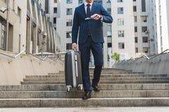 o tiro colhido do homem de negócios no terno à moda com bagagem e voo tickets ir abaixo das escadas foto de stock