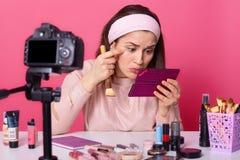O tiro da acne fêmea das observações do blogger sob seus olhos, guarda a escova cosmética e o espelho, senta-se na câmera ao grav imagem de stock royalty free