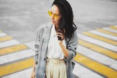 O tiro da mulher em óculos de sol amarelos e na roupa elegante retrato de uma morena na rua em um pedestre Foto de Stock Royalty Free