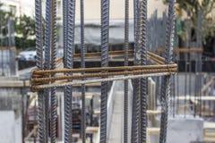 O tiro dianteiro do close-up do ferro textured novo cola na coluna concreta no canteiro de obras foto de stock royalty free