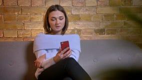 O tiro do close up da fêmea caucasiano bonita nova que conversa através do vídeo chama o telefone que senta-se no sofá na casa ac video estoque