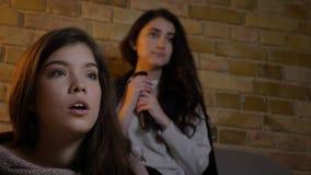 O tiro do close up de duas meninas bonitos novas que olham o witn da tevê junto chocou expressões faciais ao descansar no sofá foto de stock royalty free