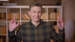 O tiro do close up do estudante masculino caucasiano atrativo novo que tem seus dedos cruzou ser esperançoso olhando a câmera den vídeos de arquivo