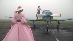 O tiro do movimento lento como uma mulher em um vestido cor-de-rosa aproxima um homem em um terno piloto do ` s de 60s que está e video estoque