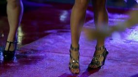 O tiro dos pés das mulheres que fazem a dança move-se no tapete vermelho molhado