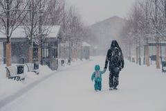 O tiro exterior da distância pequena da tampa da criança e do pai, estando na maneira à casa, mãos da posse, aprecia o tempo neva foto de stock