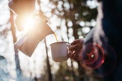 O tiro exterior da jovem mulher derrama próprio a bebida quente nas montanhas próximo à fogueira durante o por do sol fotos de stock