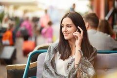 O tiro exterior da senhora moreno satisfeito tem a conversação telefônica com o amigo próximo durante o tempo livre, a notícia a  fotos de stock