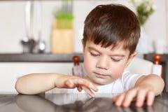 O tiro horizontal da criança masculina triguenha bonita toca na mesa de cozinha, sendo curioso, sente-a furado e com fome quando  Foto de Stock