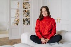 O tiro horizontal da dona de casa relaxado vestido vermelho morno na camiseta feita malha, senta os pés cruzados na pose dos lótu fotos de stock royalty free