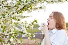 O tiro horizontal de espirros doentes da jovem mulher no lenço, vestido na camisa elegante, tem a alergia a florescer, vestido em fotografia de stock royalty free