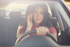 O tiro horizontal do carro ocupado da movimentação da mulher, tem a conversação telefônica, sendo enchido no engarrafamento, olha imagem de stock royalty free
