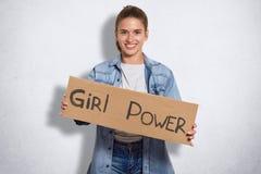 O tiro interno da mulher bonita pertence ao movimento do feminismo, tem a expressão alegre, guarda a placa com poder da menina da fotos de stock royalty free