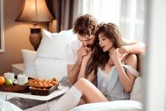 O tiro interno de pares bonitos fêmeas e masculinos apaixonado afaga-se com grande amor, senta-se na cama confortável ou Fotografia de Stock