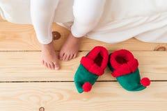 O tiro interno dos pés desencapados da criança s está no assoalho de madeira, perto do duende que s calça, acorda cedo na manhã,  imagem de stock