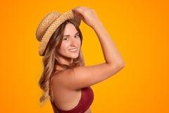 O tiro lateral do modelo fêmea novo consideravelmente de sorriso tem a pele saudável pura, veste o chapéu do verão e o roupa de b foto de stock royalty free