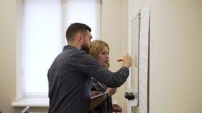 O tiro médio do homem novo e a mulher tiram um gráfico na placa branca no escritório filme