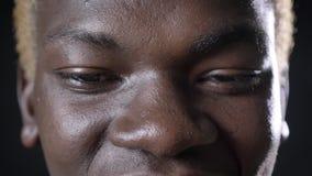 O tiro próximo do ` afro-americano feliz s do homem eyes olhando a câmera, fundo preto no estúdio video estoque