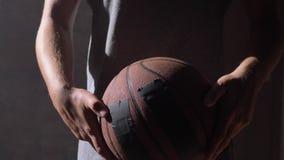 O tiro próximo do ` s do jogador de basquetebol entrega o jogo com bola vídeos de arquivo