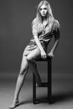 O tiro preto e branco da menina senta-se na cadeira Fotos de Stock Royalty Free