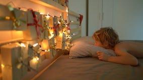 O tiro Slowmotion de um rapaz pequeno acorda e vê um calendário do advento pendurar em uma cama para iluminar com luzes de Natal filme