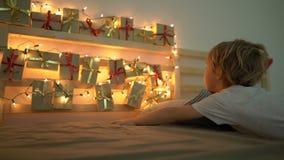 O tiro Slowmotion de um rapaz pequeno acorda e vê um calendário do advento pendurar em uma cama para iluminar com luzes de Natal vídeos de arquivo