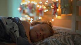 O tiro Slowmotion de um rapaz pequeno que acorda em sua cama com um calendário do advento para iluminar com luzes de Natal brilha filme
