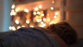 O tiro Slowmotion de um rapaz pequeno que dorme em sua cama com um calendário do advento para iluminar com luzes de Natal brilha  vídeos de arquivo