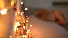 O tiro Slowmotion de um rapaz pequeno que dorme em sua cama com um calendário do advento para iluminar com luzes de Natal brilha  video estoque