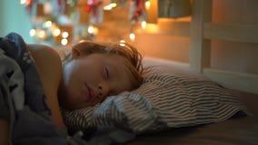 O tiro Slowmotion de um rapaz pequeno que dorme em sua cama com um calendário do advento para iluminar com luzes de Natal brilha  filme