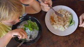 O tiro Slowmotion de uma jovem mulher e seu filho comem o alimento chinês em um café da rua filme
