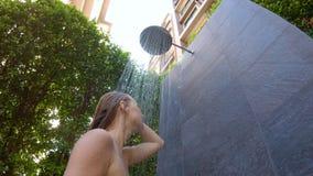 O tiro Slowmotion de uma jovem mulher toma um chuveiro em um jardim tropical Feriados em um conceito tropical do recurso Mulher n video estoque