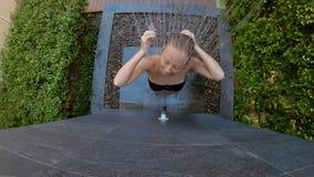 O tiro Slowmotion de uma jovem mulher toma um chuveiro em um jardim tropical Feriados em um conceito tropical do recurso Mulher n filme