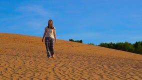 O tiro Slowmotion de uma moça em calças asiáticas anda ao longo da areia do deserto vermelho video estoque