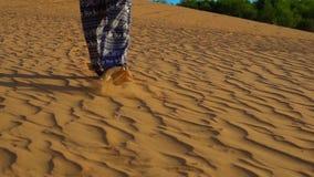 O tiro Slowmotion de uma moça em calças asiáticas anda ao longo da areia do deserto vermelho vídeos de arquivo