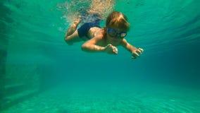 O tiro subaquático slowmotion de Ultrahd de um rapaz pequeno aprende como nadar em uma associação O menino da criança mergulha na filme