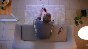 O tiro superior do close up dos jovens vestiu ocasionalmente a tevê de jogo masculina dos jogos de vídeo que senta-se no sofá den