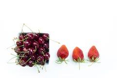 O tiro superior, fecha-se acima de cerejas doces frescas com gotas da água na bacia branca e nas morangos isoladas no fundo branc imagem de stock