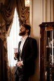O tiro vertical do homem de negócios novo farpado satisfeito veste o terno formal preto guarda o vidro e bebe a bebida, está dent imagens de stock
