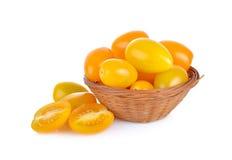 O todo e o meio corte amarelam o tomate de cereja na cesta de bambu e sobre fotos de stock