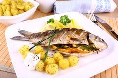 O todo grelhou os peixes seridos com batatas, limão e molho foto de stock
