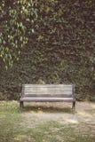O tom do vintage do jardim protege-se com um banco Imagem de Stock Royalty Free