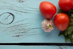 O tomate, alho, salsa sobre o fundo de madeira azul saiu fotografia de stock royalty free