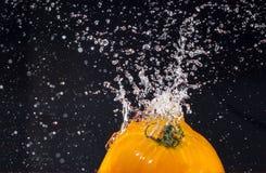 O tomate amarelo maduro espirra dentro da água fotografia de stock