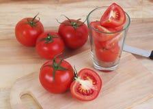 O tomate e o tomate cortado preparam-se na tabela de madeira Imagem de Stock