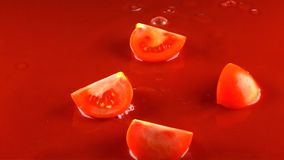O tomate vermelho cai no suco de tomate e em dividir-se em metades Movimento lento super vídeos de arquivo