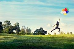 O toque do corredor e do salto da mulher balloons a flutuação no céu no campo de grama verde e de flor Imagens de Stock