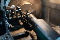 O torno automotivo do metal das partes de giro é uma ferramenta que gire o workpiece sobre uma linha central de rotação para exec imagem de stock royalty free